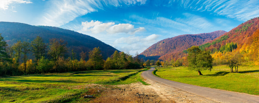 road winding through the country valley panorama. wonderful autumn landscape in mountains. forest on hills in colorful foliage. sunny weather with fluffy clouds on the sky
