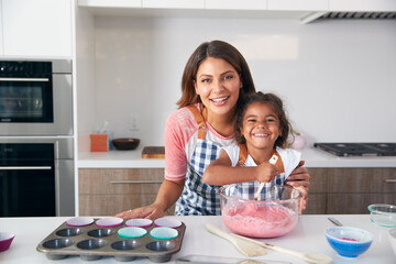 Portrait Of Hispanic Mother And Daughter Having Fun In Kitchen At Making Cake Together