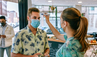 Coffee shop owner checking customers for fever upon entering