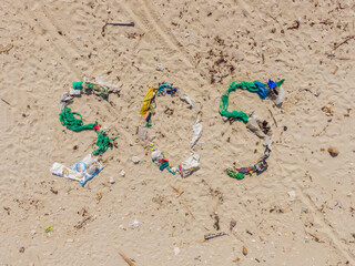 Environmental problem. Ecology concept. Plastic on the beach with sos writing. Spilled garbage on...