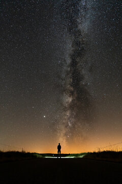 Rear view of 1 person silhouette at night with milky way