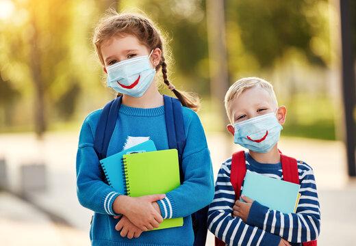 Happy schoolchildren in protective masks