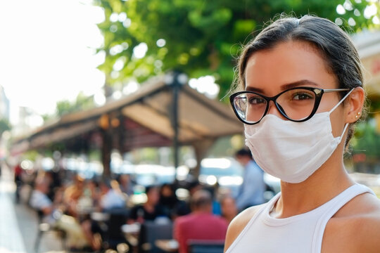 Portrait of young beautiful woman of Arabic ethnicity wearing disposable face mask as barrier to protect against contact with infectious materials at the streets. Close up, copy space, background.