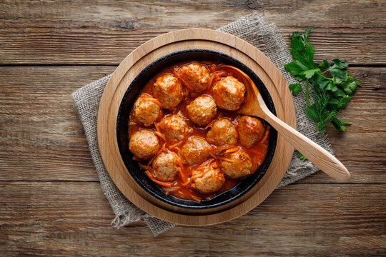 Meatballs in a pan in sweet and sour tomato sauce. Top view.