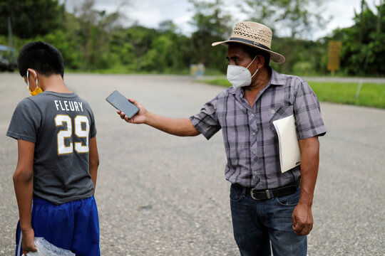 Juan holds his phone with a call from his wife Elida as their disabled 12-year-old son Gustavo walks away to avoid the conversation with her, during their reunion in Peten