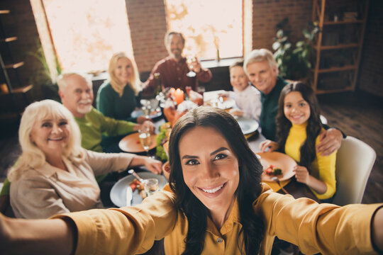 Self-portrait of nice attractive cheerful big full family brother sister gathering parents grandparents eating homemade meal festal autumn fall November at modern loft brick industrial interior
