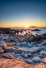 Wall Mural - Sunset over the rocky beach at Mealista