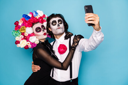 Photo of cute funny zombie couple man lady girl embrace hold telephone make selfie translate festival wear black dress death costume roses headband suspenders isolated blue color background