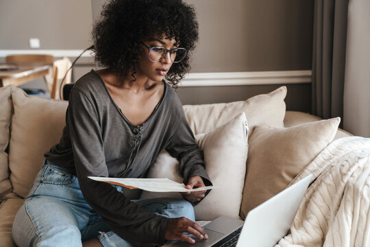 Image of thinking african american woman working with laptop and papers
