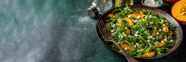 Homemade pumpkin salad with grilled pumpkin slices, arugula and cheese. Autumn pumpkin salad recipe, dark background copy space