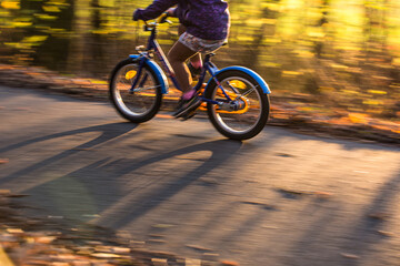 Little boy going fast on his little bike on a forest path in warm evening light