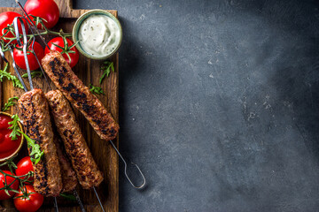 Shish kebab on skewers, from minced beef meat. Lula kebab, traditional Caucasian recipe. On black...