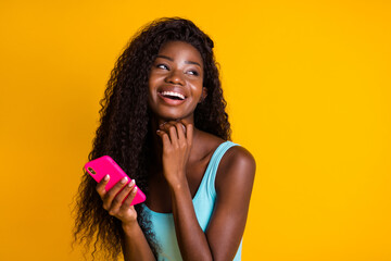 Door stickers Wall Decor With Your Own Photos Photo portrait of african american woman with long wavy hair holding pink smartphone in two hands laughing wearing blue singlet isolated on vivid yellow colored background