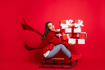 Full length body size profile side view of her she attractive glad cheerful girl riding sledge having fun delivering giftboxes Eve Noel isolated bright vivid shine vibrant red color background