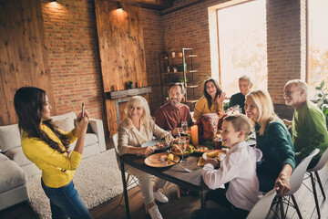 Photo of full family gathering eight people small daughter hold telephone make picture harmonic holiday mother wave hand dinner big table turkey generation home evening living room indoors