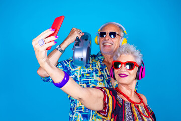 Couple of senior man and woman on blue background taking selfie - Grandpa and grandma live streaming isolated with stereo