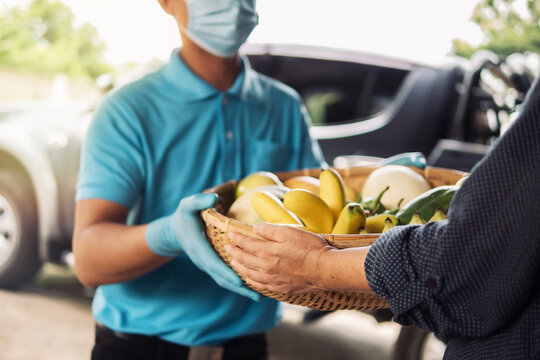 Senior woman hand receiving fresh fruits and vegetables in bamboo basket from delivery man wearing protective gloves and face mask. Food delivery in COVID-19 pandemic and senior people social care.