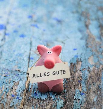 Kleines rosa Glücksschwein, mit Tafel und Aufschrift: alles Gute, auf altem, blauen Holz.