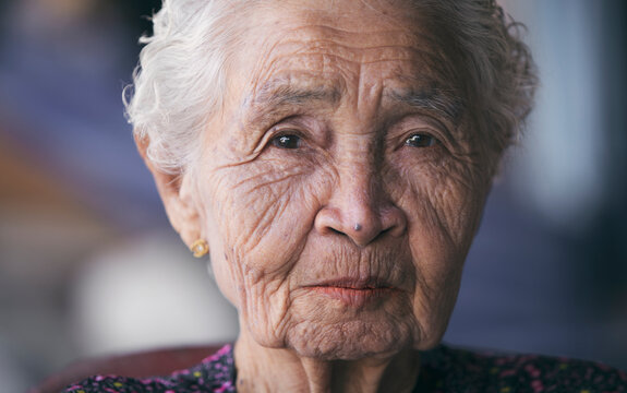 Asian old or elderly woman sitting alone smiling, wrinkled skin, white hair looking at camera, grandmother's face, close-up