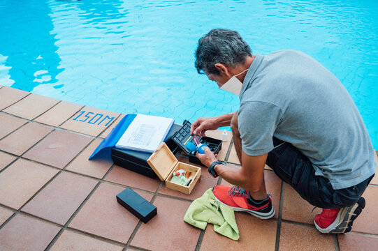 man checked the pH of the pool water using electronic devices and disinfection of the water against covid 19