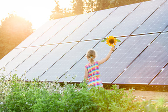 Young 6 year old blonde girl child standing in front of small solar panel farm in countryside. Renewable energy concept. Bright yellow warm sun lens flare.