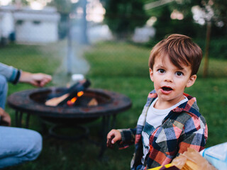 eating s'mores by campfire