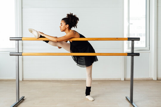 Female ballet dancer with black hair stretching her leg. Side view of young woman preparing for a ballet class in studio.