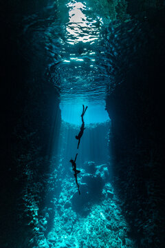 A couple of freedivers handing diving in the cave with sun rays