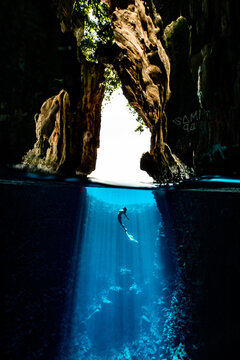 A mermaid diving in the cave with sun rays