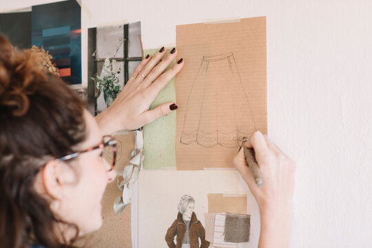 Focused Young Woman Drawing On Paper For Moodboard