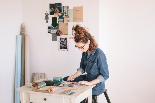 Focused Young Woman Choosing Color Sample For Moodboard On Wooden Table