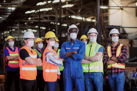 Group of industrial foreman and worker team consist of Technicians, Engineers and factory Manager wearing helmet and surgical mask. to protect Coronavirus or Covid-19 inflection in Industry plant.