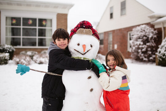 child hugs snowman with hat, scarf, gloves and carrot nose