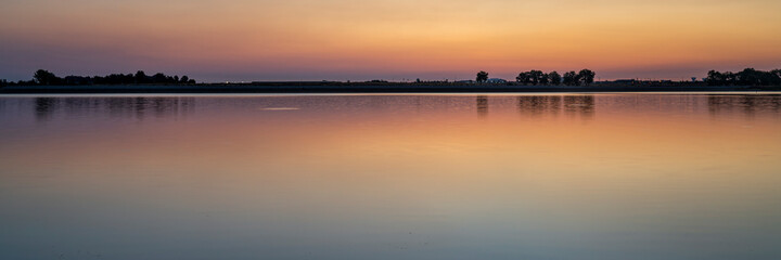 summer dawn over a calm lake - Boyd Lake State Park, popular boating and recreation area in northern Colorado