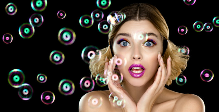 Beautiful young woman with colored rainbow eyelashes and bright makeup in soap bubbles on black background.