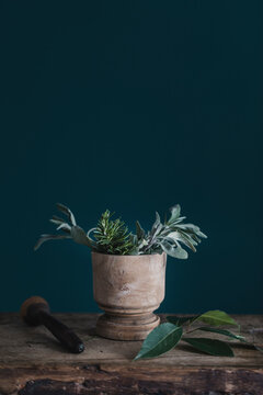 Still Life Of Fresh Herbs And Mortar On Wooden Board On Blue Background