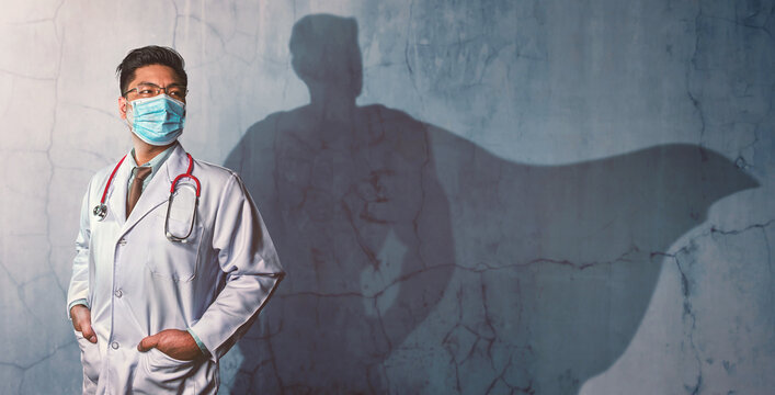 Brave Doctors with his shadow of superhero on the wall. Concept of powerful man