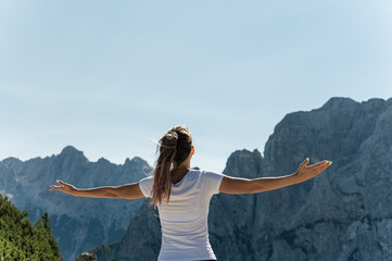 Female hiker enjoying life standing with arms wide open enjoying the view of the Alps