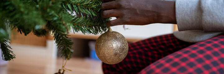 Girl hanging shiny golden holiday bauble on christmas tree