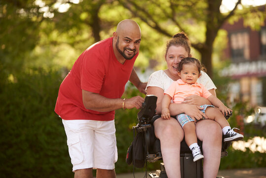 Disabled mother holding child on her lap as they race through park with dad.