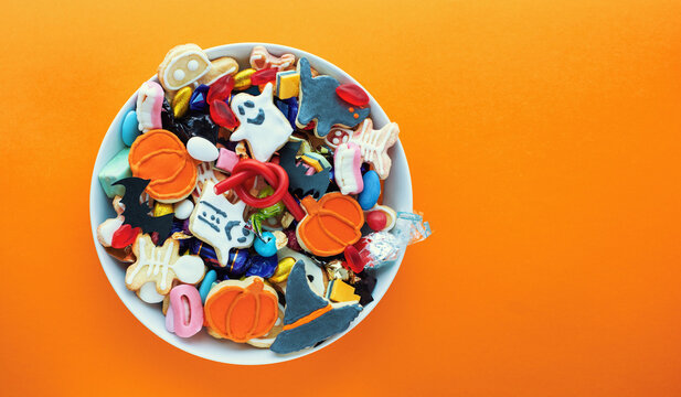 Halloween Jack o Lantern candy bowl with candy and halloween cookies Trick or Treat on orange background
