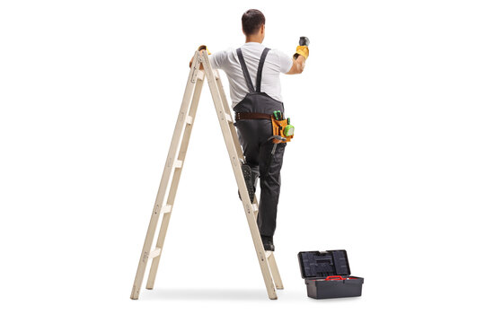 Rear view shot of a repairman on a ladder drilling with a machine into a wall