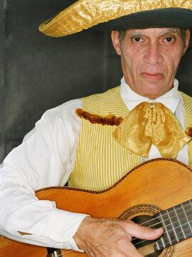 Senior man in traditional clothing playing guitar