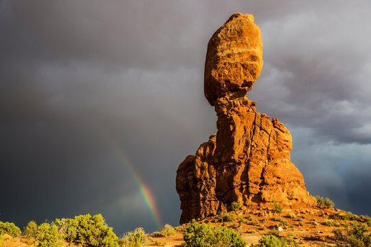 Rainbow forming behind the Balanced Rock of Arches National Park.