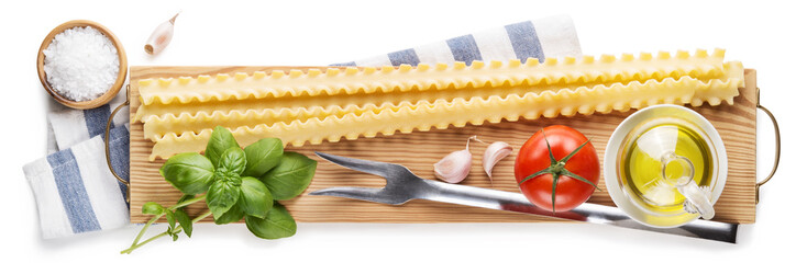 Durum wheat semolina pasta, Mafalde, with basic ingredients, olive oil, tomato, garlic and basil on wooden cutting board isolated on white background. Top view.