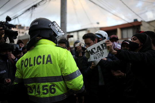 A demonstrator holds up a sign while protesting outside a police station after a man, who was detained for violating social distancing rules, died from being repeatedly shocked with a stun gun by officers, according to authorities, in Bogota