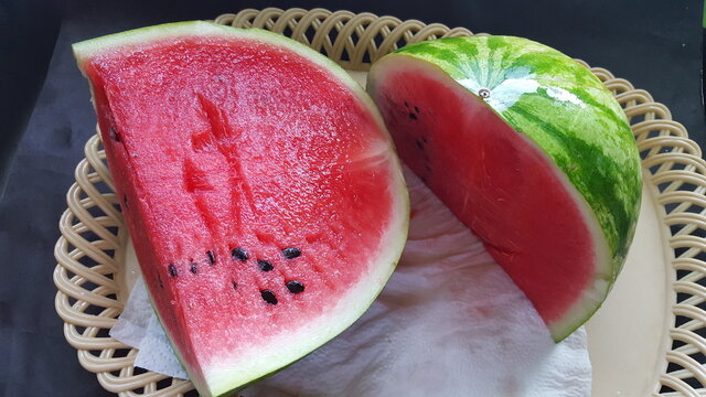 Two pieces of cut watermelon on a tray.