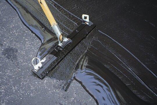 Man sealing asphalt driveway/Sealcoating