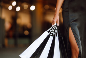 Shopping bags in the hands. Fashion woman with packages after shopping. Black friday, sale,...