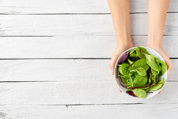 Overhead shot of female hands holding green salad in bowl on white wooden background with copyspace